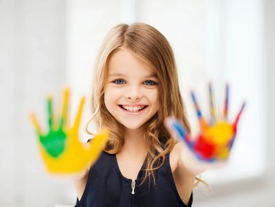 Young girl with paint on both hands enjoying the creative process.