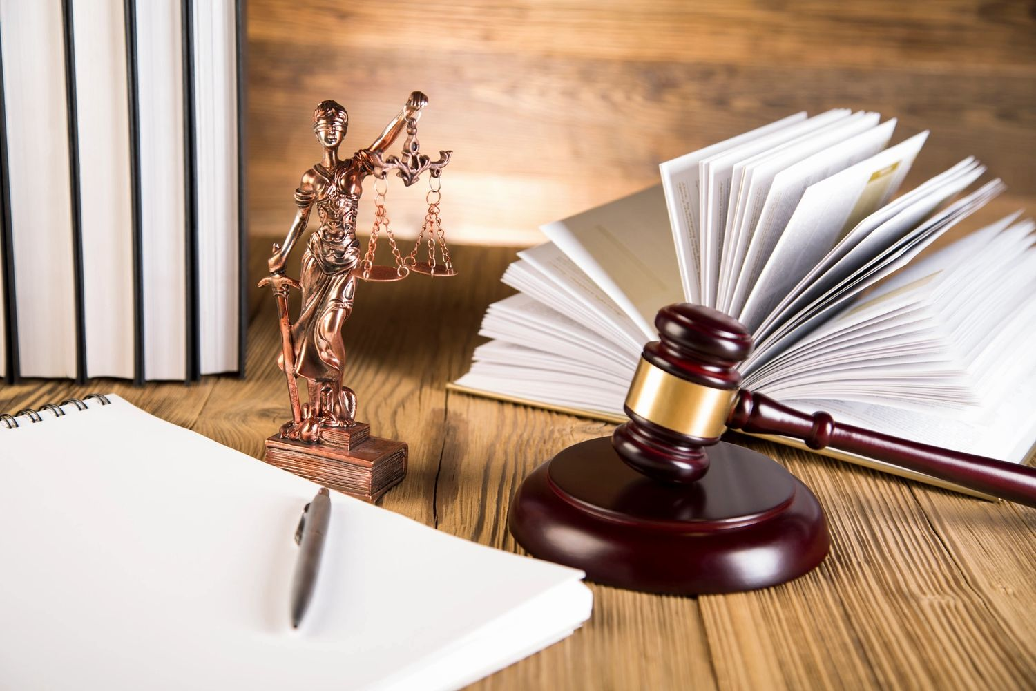 A picture of a small statue of Lady Justice, with her scales, a gavel, and an assortment of law book