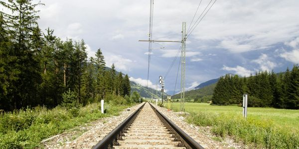 the image shows a modern electric rail line in a rural setting with concrete railroad ties and and overhead catenary for supply of electricity to the locomotive;  railhaul is designing a similar system for individually  electric powered freight rail cars for use in mines, ports and remote communities