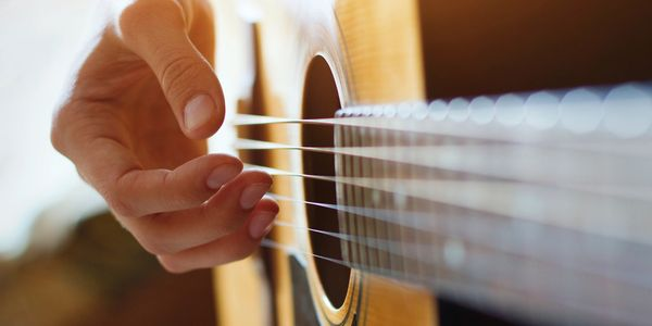 A closeup of a hand strumming and acoustic guitar.