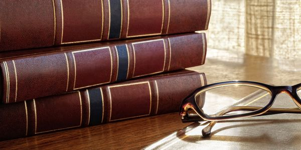 Set of Legal Books with Reading Glasses sitting on a table