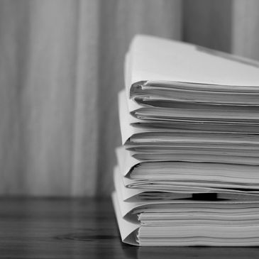 Black and white picture of a pile of folders stuffed with papers on a desk