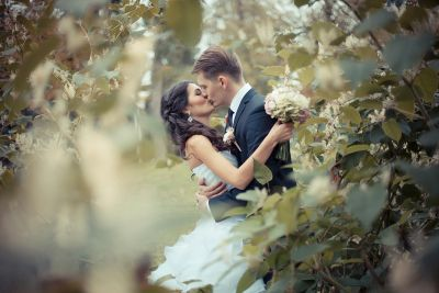 Bride and groom engaged in a passionate kiss.