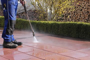 Man in Blue Waterproof Pants Pressure Washing a Driveway, Pressure Washing Service, Clear as Day