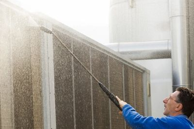 Man pressure cleaning wall