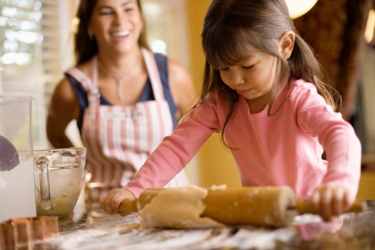 Woman baking with young girl.