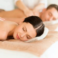 Couples Massage - women and man laying on two massage tables with smiles on their faces