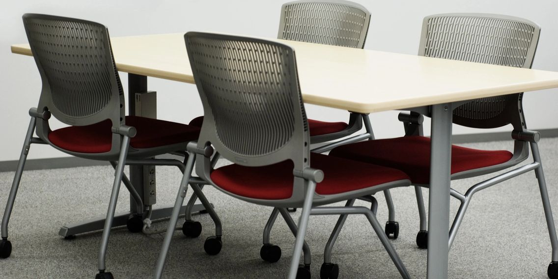 Office chairs surrounding a table. The office has grey colored commercial glued down (CGD) carpet.