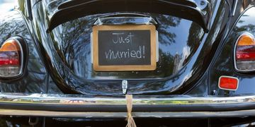 married couple in a car with a just married sign