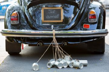 Just married sign on a car and tin cans