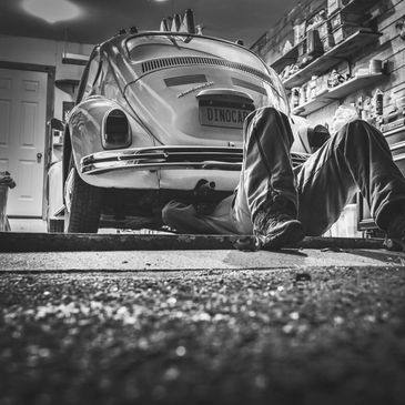 Mechanic lying down and working under car at auto service garage