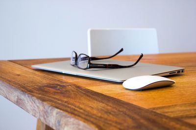 Eye glasses on top of a laptop sitting on a wooden desk.