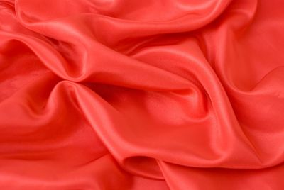 Red fabric laying on table and wrinkled