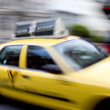 blurred image of a taxi driving down the road