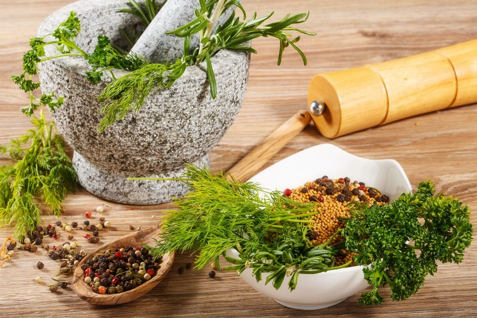 Mortar and pestle with herbs, bowl of parsley and seeds, spoon filled with peppercorns.
