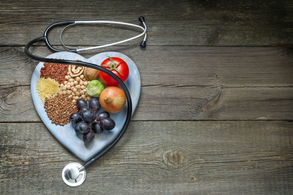 On an antique wooden table lie a stethoscope draped over a heart-shaped platter covered in fruit, ve