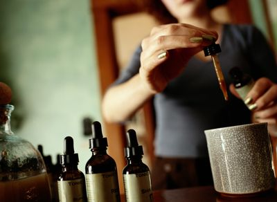 Woman putting drops of an herbal tincture into a mug.