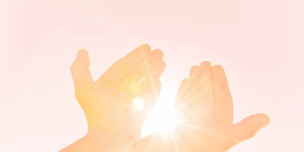 Beautiful golden light beams down into the cupped hands being held up to the soft and serene blush pink sky. Conveying a feeling of warmth and lightness, healing and deep relaxation. The same feelings that one experiences during a Reiki session.