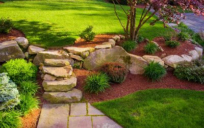 Backyard landscaping with boulders, stone steps and a paver walkway.