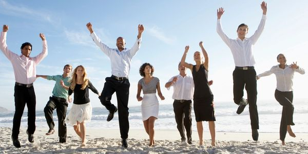Business people jumping for joy at a beach