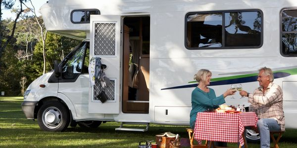 couple eating next to a caravan
