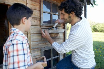Mentor teaching his mentee how to use a hammer.