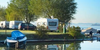 Image for recreational and toy insurance coverage depicting a boats and RVs and 5th wheel trailers next to a lake