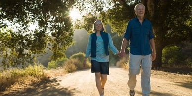 A senior man and woman walk along a sunlit path holding hands and smiling as they exercise