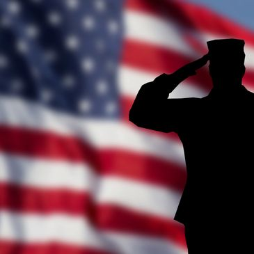 Silhouette soldier saluting in front of a flag