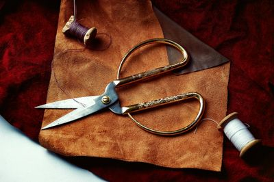 Piece of leather being cut with scissors.