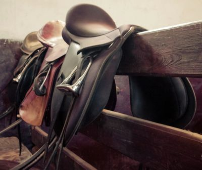 English jumping saddles sitting on a rail fence