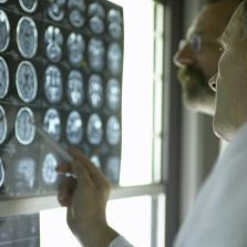 Two male scientists are looking at a wall with back lit images of many brain scans.