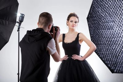 A photographer taking head shot pictures in a studio.