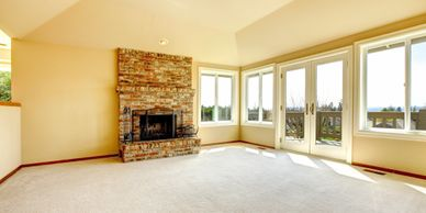 view of bright living area with fireplace and large windows and patio doors with no curtains