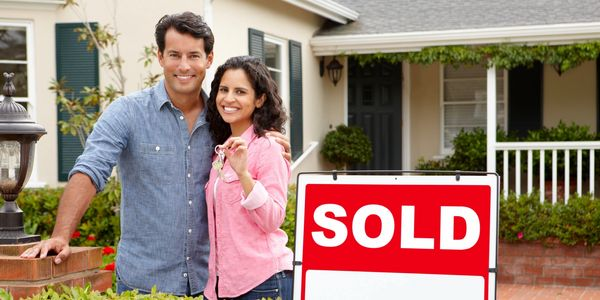 couple in from of house with sold sign