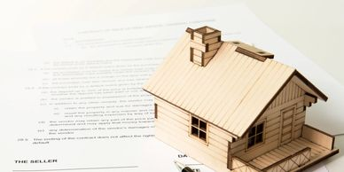 Real Estate Purchase Contract with a wooden house model and ink pen
