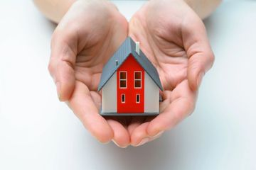 hands gently holding a miniature model of a house with a red front door