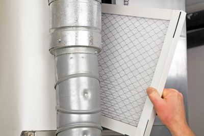 Person sliding a filter into an HVAC unit past ductwork