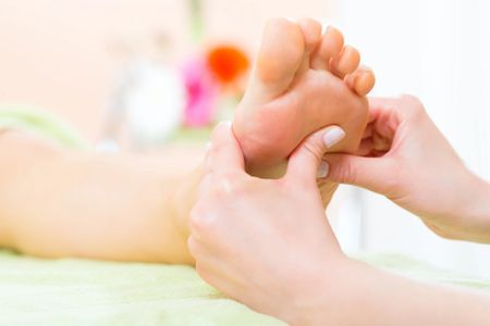 Therapist performing Reflexology on a client