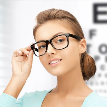 woman wearing eyeglasses holding them with one hand and standing in front of an eye chart