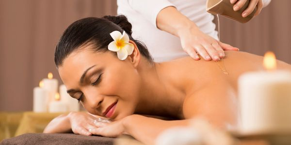Woman having a back massage with therapeutic oil
