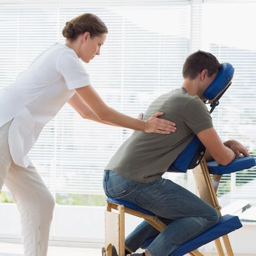 Person receiving a chair massage fully clothed.