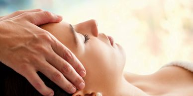 Therapist giving client craniosacral therapy