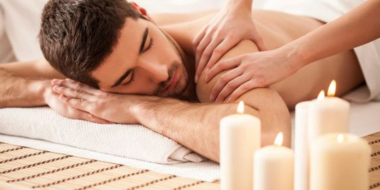 Fully licensed LMT massage therapist in Tacoma, WA.  Man getting massaged with candles.