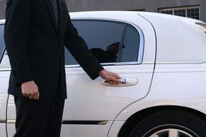 Chauffeur Driver in black suit opening white car door of Luxury SUV at Busselton Jetty