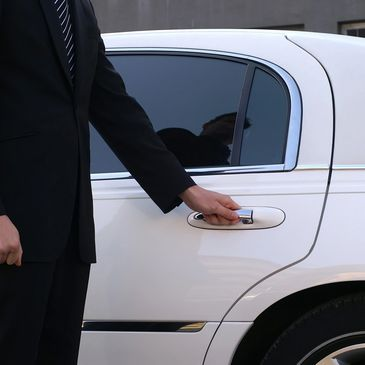 Chauffeur Driver in black suit opening white luxury car door