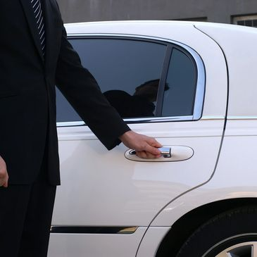 Chauffeur in black suit opening car door
