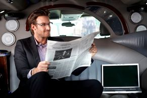 Executive wearing suit and glasses and reading newspaper in the back of Chauffeur driven car at Buss