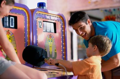 Male adult and two children around an arcade game