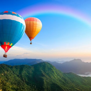 hot air balloons with rainbow over mountains